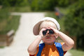 Little boy searching searches with binoculars looks through Royalty Free Stock Photo