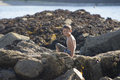 Little boy on seaside rocks on a sunny day sitting playing by the sea holidays in killybegs in the west of ireland beautiful Royalty Free Stock Photography