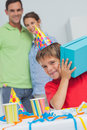 Little boy shaking his birthday gift during party Royalty Free Stock Images