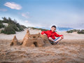 Little boy in shorts and a jacket sitting legs crossed near the sandy castle against the blue sky and the sand dunes Royalty Free Stock Photo