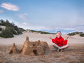 Little boy in shorts and a jacket sitting legs crossed near the sandy castle and meditates against the blue sky and the sand dunes Royalty Free Stock Photo