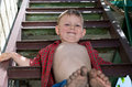 Little boy showing off his dirty feet sitting on step holding them out to camera with their muddy soles after playing barefoot Royalty Free Stock Photography