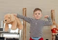 Little boy showing off his muscles playfully as he flexes arm while holding up big plush soft toy dog other with serious Royalty Free Stock Photos