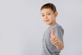 Little boy showing thumb up gesture in a gray T-shirt on white background. Royalty Free Stock Photo