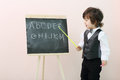 Little boy shows by pointer letters at chalkboard and talks in studio Royalty Free Stock Image