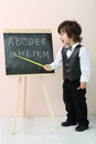 Little boy shows by yellow pointer letters at chalkboard and calls it in studio Stock Photos
