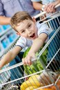 Little boy sits in the cart with watermelon shopping trolley and other products bought by parents Royalty Free Stock Image