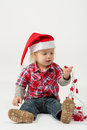 A little boy sits in modern clothes with garland his hand Stock Image