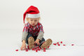 A little boy sits in modern clothes and hats santa claus play with garland Stock Photos