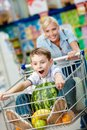 Little boy sits in the shopping trolley with watermelon and other products while mother drives it Stock Photography
