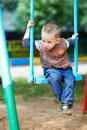Little boy sits on a swing Stock Images
