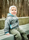 Little boy sitting on a bench in the park Stock Photo