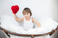 Little boy sitting in a big chair on white background holding red heart Royalty Free Stock Images