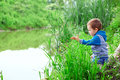 Little boy sitting in cane on riverside throwing stones lonely Stock Photos