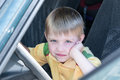Little boy sitting in the car driving. One hand props her cheek. Royalty Free Stock Photo