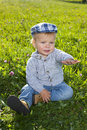 Little boy sitting in the grass grassoutdoor Stock Photography