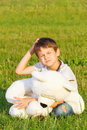 Little boy sitting on the grass with teddy bear and planning or thinking about something Royalty Free Stock Photo