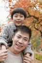 Little boy sitting on his fathers shoulders walking through the park in autumn close up portrait Royalty Free Stock Image
