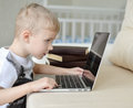 Little  boy sitting with laptop on the couch at home Royalty Free Stock Photo
