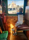 Little boy sitting on the machinist or train engineer seat in old steam locomotive and looking out of the window Royalty Free Stock Photo