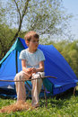 Little boy sitting near blue tent on nature Stock Photos