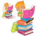 Little boy is sitting on a pile of books and reading another book Royalty Free Stock Photo