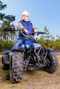 Little boy sitting on quad bike in the forest Stock Images