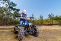 Little boy sitting on quad bike in the forest Royalty Free Stock Images