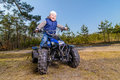 Little boy sitting on quad bike in the forest Stock Photography