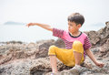 Little boy sitting on the rock on the beach face look happy Royalty Free Stock Photo