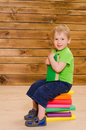Little boy sitting on stack of colored books Royalty Free Stock Photo