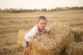 Little boy sitting on the stubble summer mown wheat Stock Photo