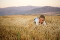 Little boy sitting on the stubble summer mown wheat Royalty Free Stock Photos
