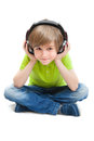Little boy sitting on the white floor listening to music Royalty Free Stock Photo