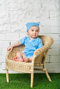 Little boy sitting in wicker chair a on the lawn barefoot Stock Images