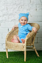 Little boy sitting in wicker chair a on the lawn barefoot Royalty Free Stock Images
