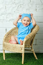 Little boy sitting in wicker chair a on the lawn barefoot Stock Photos