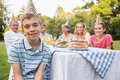 Little boy smiling at camera at his birthday party outside picnic table Royalty Free Stock Images