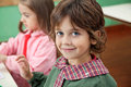 Little boy smiling with classmate in background portrait of female at kindergarten Royalty Free Stock Photos
