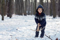 Little boy in the snow with crossbow playing Stock Images