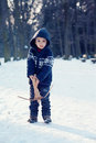 Little boy in the snow with crossbow playing Royalty Free Stock Image