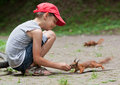 Little boy and squirrels cute feeding at park Royalty Free Stock Images