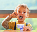 Little Boy sta mangiando il yogurt. Fotografie Stock