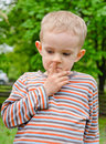 Little boy standing picking his nose candid image of a thoughtful outdoors in a garden or park Royalty Free Stock Photo