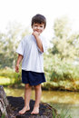 Little boy standing on trunk at lake outdoor Royalty Free Stock Photos