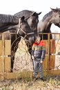 A little boy stands near the black beautiful horses and smiles sweetly. Outdoors. Royalty Free Stock Photo
