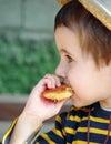 Little boy in straw hat eats Stock Photo