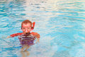 Little boy swimming with mask in pool