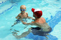 Little boy swimming with swim instructor male holding boys hands during lesson Stock Photography