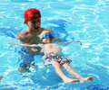 Little boy swimming with swim instructor male teaching how to float in the water during lesson Stock Photography